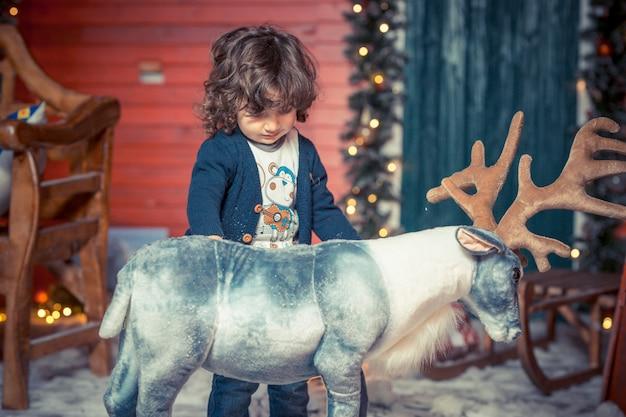 Ein kleiner gelockter süßer kinderjunge in den jeans, die mit rotwild spielen, spielen im wohnzimmer auf weihnachten. familienfeier