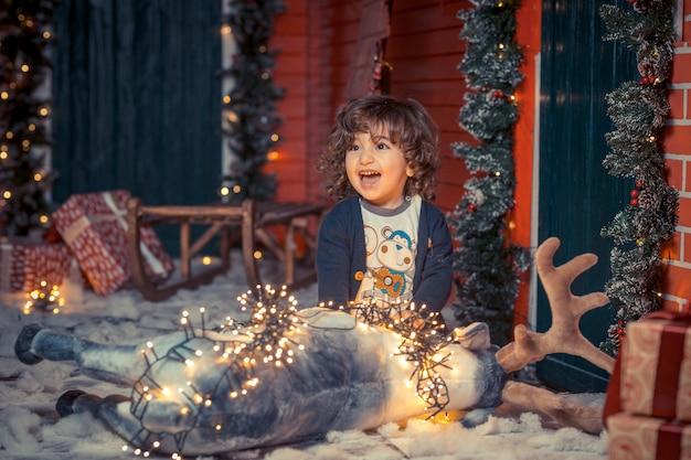 Ein kleiner gelockter süßer kinderjunge in den jeans, die mit rotwild spielen, spielen und weihnachtslichter im wohnzimmer auf weihnachten