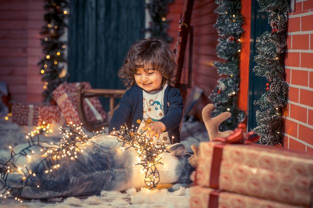 Ein kleiner gelockter süßer kinderjunge in den jeans, die mit rotwild spielen, spielen und weihnachtslichter im wohnzimmer