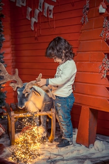 Ein kleiner gelockter süßer kinderjunge in den jeans, die mit rotwildspielzeug und weihnachtslichtern im wohnzimmer auf weihnachten stehen und spielen