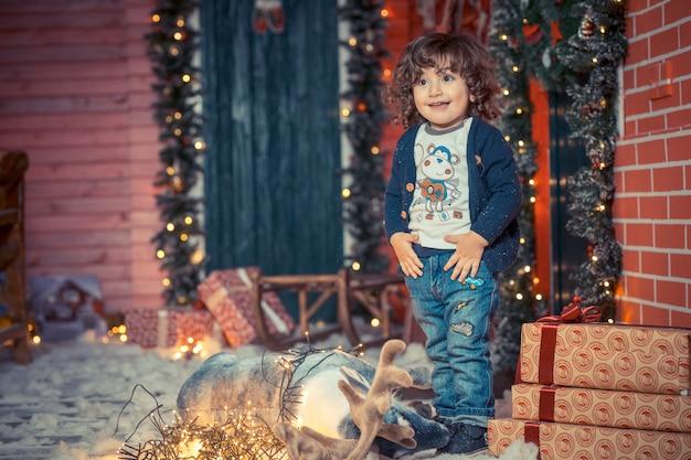 Ein kleiner gelockter süßer kinderjunge in den jeans, die nahe dem rotwildspielzeug und den weihnachtslichtern im wohnzimmer auf weihnachten stehen