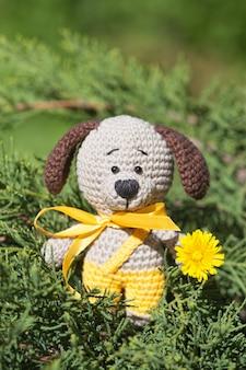 Ein kleiner gestrickter brauner hund mit einem gelben band im sommergarten. gestricktes spielzeug, handgemacht, amigurumi