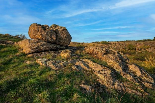 Ein kleiner haufen alter steine in einem großen grün-gelben feld vor der kulisse eines traumhaft schönen blauen himmels