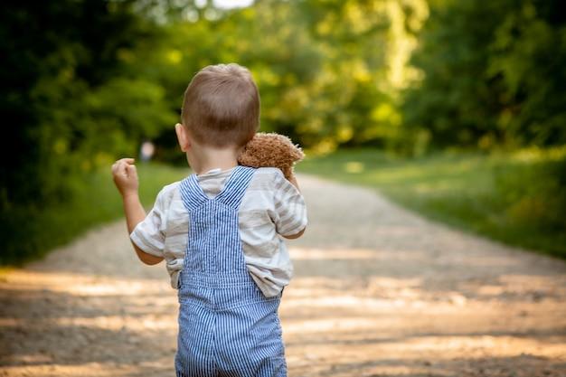 Ein kleiner junge auf einer straße im wald