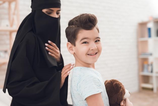 Ein kleiner junge aus einer arabischen familie hält einen spielzeugbären in der hand