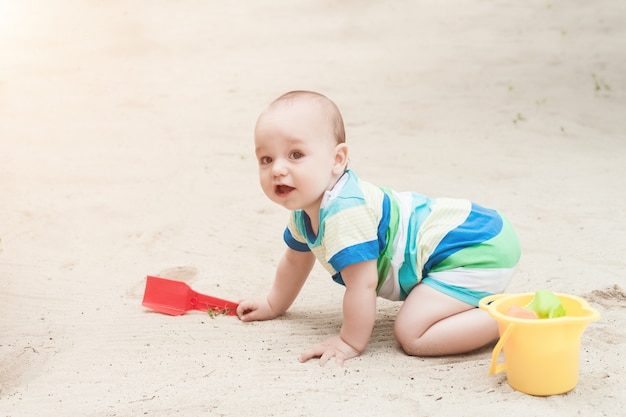 Ein kleiner junge, der auf einem weißen sand spielt
