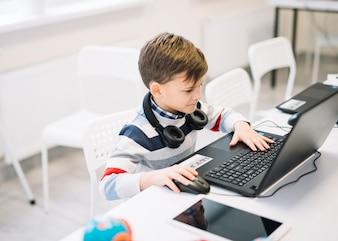 Ein kleiner Junge, der Laptop auf Schreibtisch im Klassenzimmer verwendet
