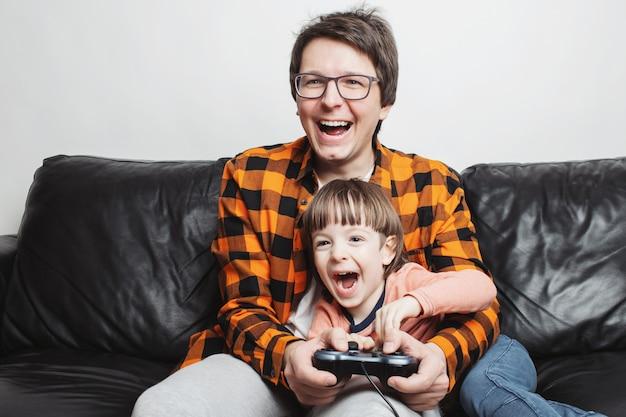 Ein kleiner junge, der videospiele mit vati spielt.