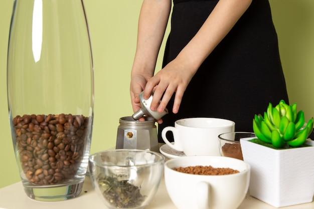 Ein kleiner junge der vorderansicht, der kaffeegetränk auf dem tisch auf dem steinfarbenen raum vorbereitet