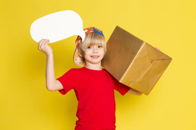 Ein kleiner junge der vorderansicht in der bunten kappe des roten t-shirts und der grauen jeans, die box auf dem gelben hintergrund halten