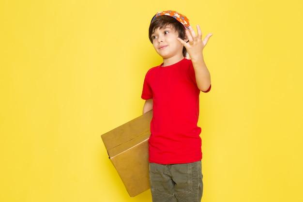 Ein kleiner junge der vorderansicht in der bunten kappe des roten t-shirts und in der khakihose, die box auf dem gelben hintergrund hält