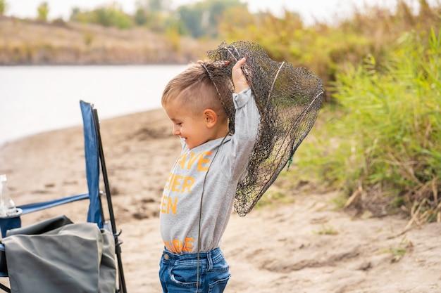 Ein kleiner junge fischt und möchte den größten fisch fangen. netter kleiner junge verwirrt im fischnetz. sommerferien-konzept.