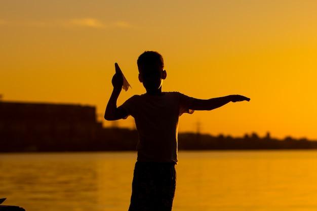 Ein kleiner junge hält einen origami in form eines flugzeugs in der hand und steht am fluss bei sonnenuntergang.