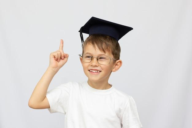 Ein kleiner junge hat eine schwarze abschlusskappe mit einer quaste auf einem weißen isolierten hintergrund. verwenden sie es für ein schul- oder bildungskonzept.