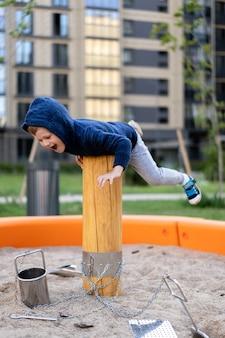 Ein kleiner junge hat spaß am spielen auf dem modernen städtischen europäischen spielplatz