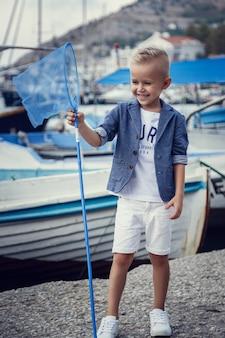 Ein kleiner junge im marinestil vor dem hintergrund von booten und yachten. idee und konzept freundschaft, urlaub, urlaub, familie