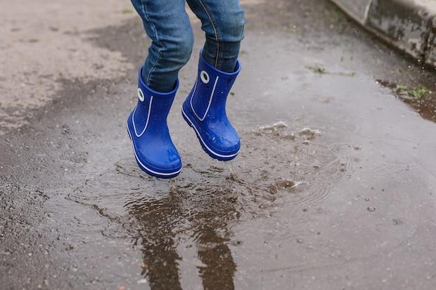 Ein kleiner junge in blauen gummistiefeln springt in eine pfütze. nahaufnahme der füße.