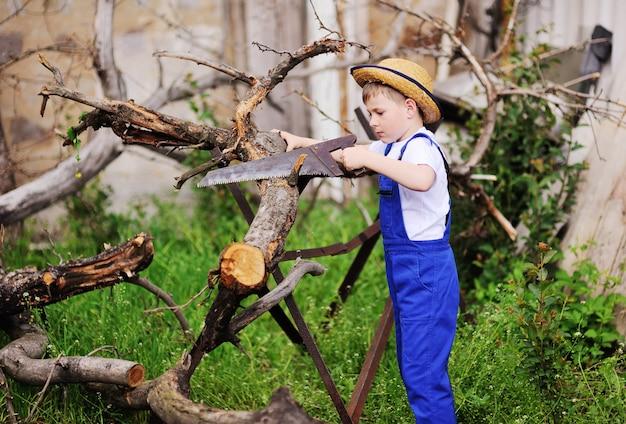 Ein kleiner junge in blauer arbeitskleidung und einem strohhut, der holzsäge sägt.