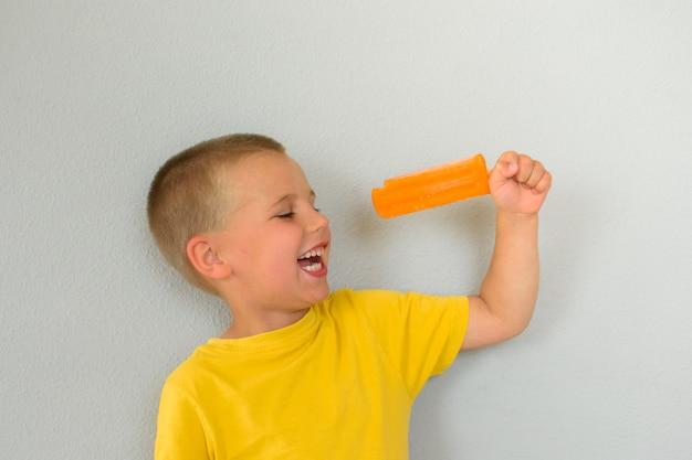 Ein kleiner junge in einem gelben t-shirt mit einem orangefarbenen eis am stiel, genannt eskimo. ein kleines dreckiges fröhliches gesicht. reiner grauer hintergrund.
