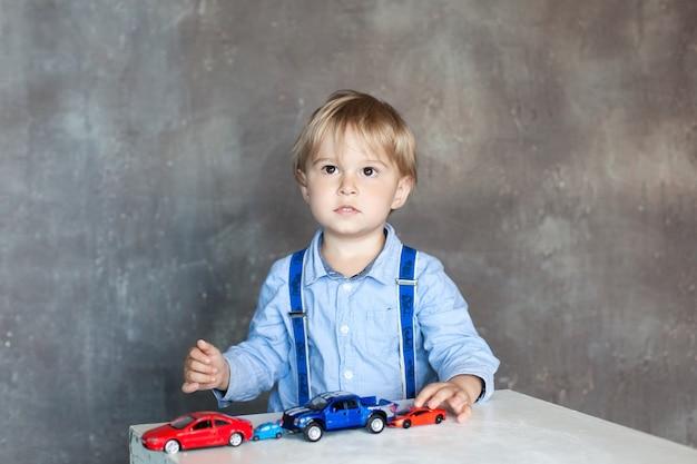 Ein kleiner junge in einem hemd mit hosenträgern spielt mit mehrfarbigen spielzeugautos. vorschuljunge, der mit spielzeugauto auf einem tisch zu hause oder in der kindertagesstätte spielt. lernspielzeug für kinder im vorschul- und kindergartenalter.