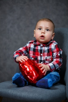 Ein kleiner junge in einem hemd spielt mit einem ballon in form eines herzens