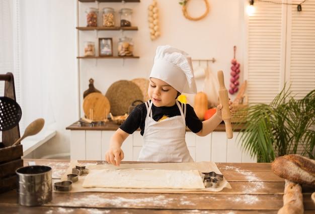 Ein kleiner junge in einem kochkostüm sitzt an einem tisch mit einem nudelholz und teig in der küche