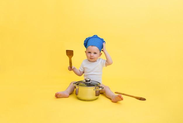 Ein kleiner junge in einem weißen body und einer kochmütze mit einem topf und einem holzspatel mit einem löffel.