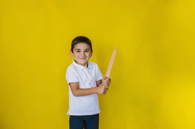 Ein kleiner junge in einem weißen hemd steht an einer gelben wand.