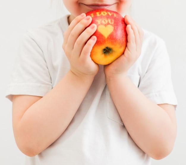 Ein kleiner junge in einem weißen t-shirt hält einen apfel in den händen mit der aufschrift ich liebe dich. vertikales foto