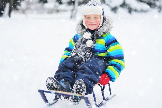 Ein kleiner junge in einer hell gestreiften jacke, der auf einem schlitten sitzt, lächelt