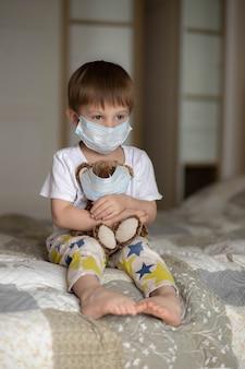 Ein kleiner junge in einer maske sitzt auf dem bett und umarmt einen teddybären. bild mit selektivem fokus. foto in hoher qualität