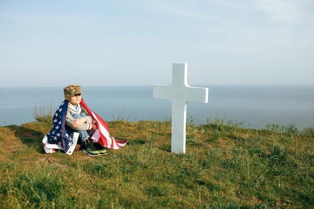 Ein kleiner junge in einer militärmütze, bedeckt von der flagge der vereinigten staaten, sitzt auf dem grab seines verstorbenen vaters. 27. mai gedenktag