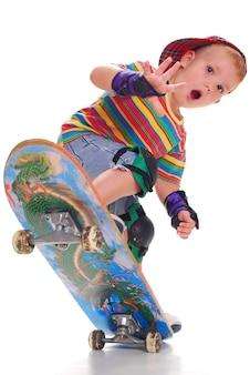 Ein kleiner junge in hellen kleidern auf einem skateboard drückt.