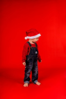 Ein kleiner junge in jeansoverall und weihnachtsmütze steht seitlich
