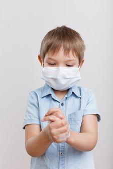 Ein kleiner junge in medizinmaske wäscht seine hände mit antibakterieller seife. coronavirus-konzept. das kind schützt seine gesundheit.