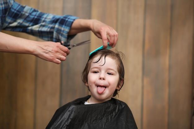 Ein kleiner junge ist getrimmt in den strahlenden emotionen des friseurs auf seinem gesicht