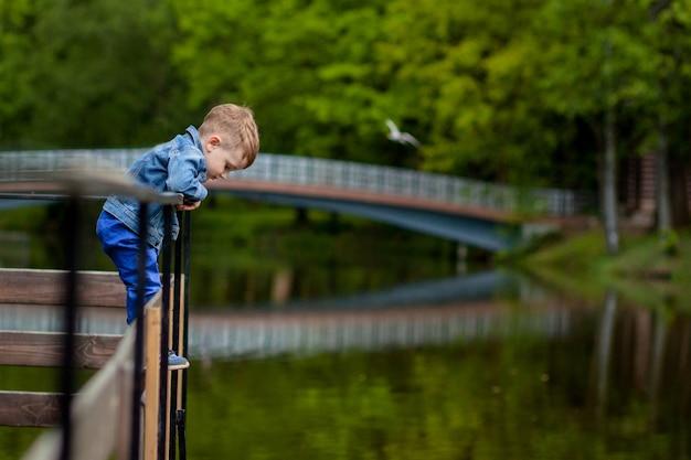 Ein kleiner junge klettert auf ein brückengeländer im park. die gefahr des ertrinkens. gefahr für kinder