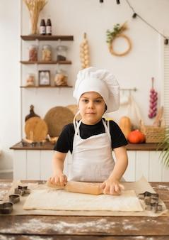 Ein kleiner junge kocht in einer kappe und einer schürze rollt teig mit einem nudelholz in der küche aus