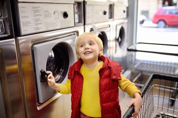 Ein kleiner junge lädt kleidung in die waschmaschine im öffentlichen waschsalon