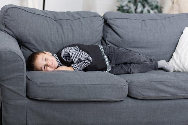 Ein kleiner junge liegt auf einem sofa mit einer grauen strickdecke und lächelt
