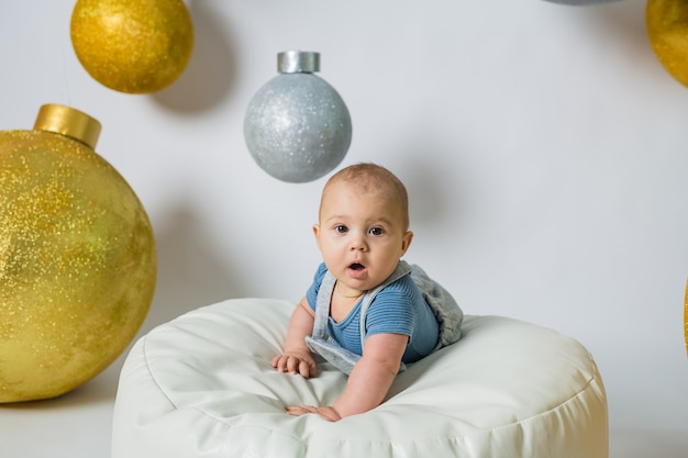 Ein kleiner junge liegt auf einer stuhltasche auf weißem hintergrund mit großen hängenden bällen
