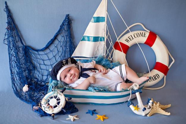 Ein kleiner junge liegt in matrosenkleidung in einem boot