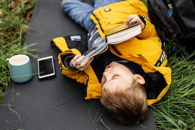 Ein kleiner junge liest auf einer lichtung ein buch. er liegt auf einem touristenteppich im grünen gras, eine tasse steht daneben, ein telefon liegt. ruhe, training im freien im wald.