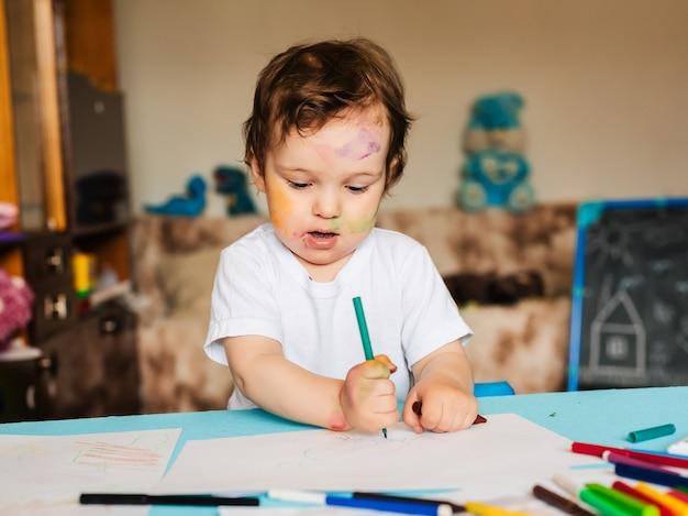 Ein kleiner junge malt mit bunten markern auf ein blatt papier