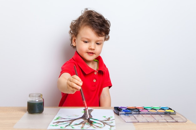Ein kleiner junge malt mit einem pinsel einen baum mit grünen blättern und malt auf ein weißes blatt papier am tisch.