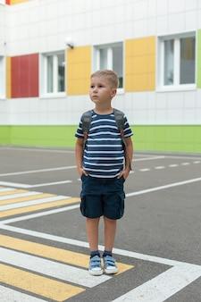 Ein kleiner junge mit einem rucksack, der allein in der nähe der schule die straße überquert