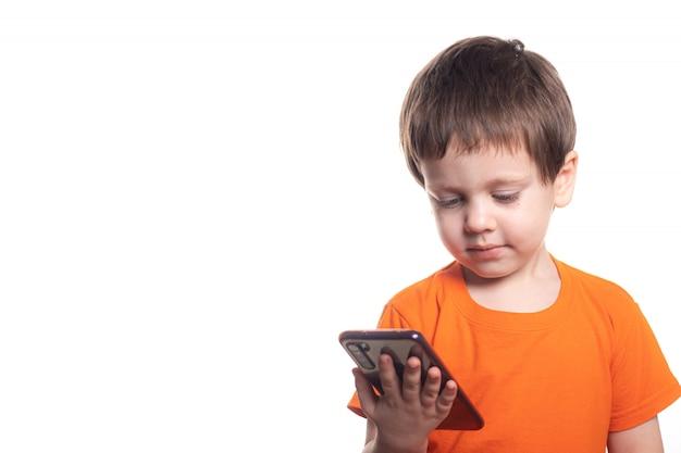Ein kleiner junge mit einem telefon auf einem weißen hintergrund. jungen telefonieren