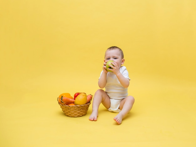 Ein kleiner junge mit einem weidenkorb mit gemüse und obst auf einem gelben platz. der junge sitzt in einem weißen body und isst einen apfel. freier platz auf einem gelben platz.