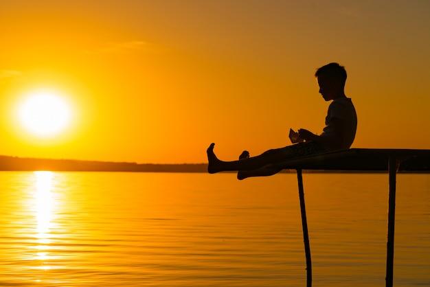 Ein kleiner junge mit erhobenen beinen spielt auf der brücke und untersucht sein papierboot in seiner hand bei sonnenuntergang auf dem see