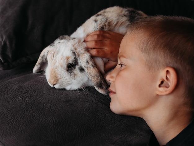 Ein kleiner junge mit kaninchen